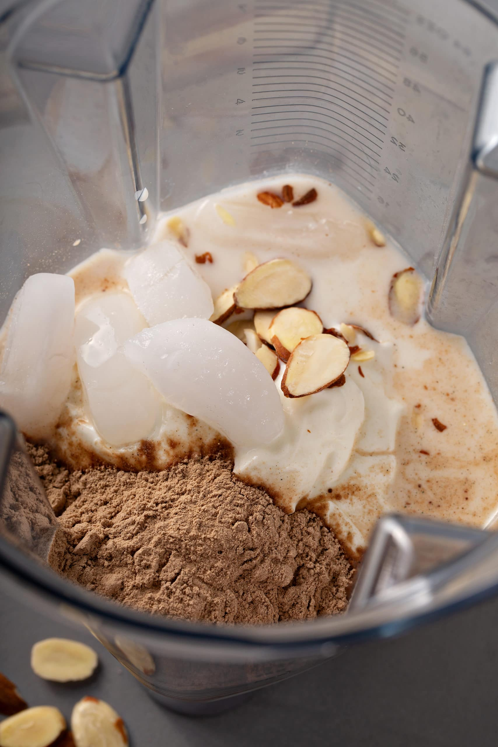 ingredients in a blender to make a chocolate coconut protein shake, ice cubes, almonds, chocolate protein powder, yogurt and milk