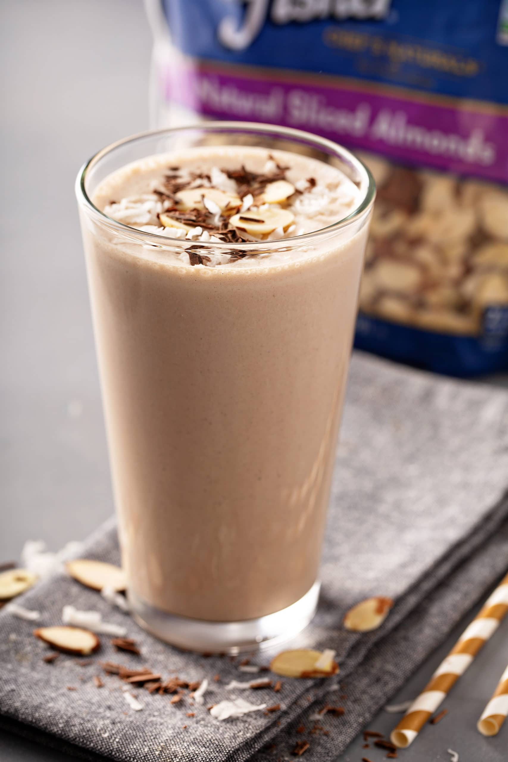 A tall glass of almond joy protein shake with sliced almonds on top.