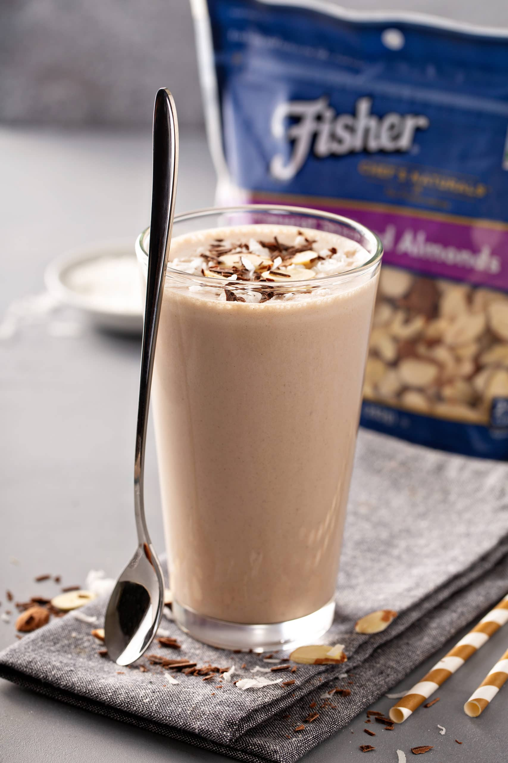 Tall glass of Almond Joy Chocolate Protein Shake with sliced almonds on top and a package of Fisher's Sliced almonds in the background