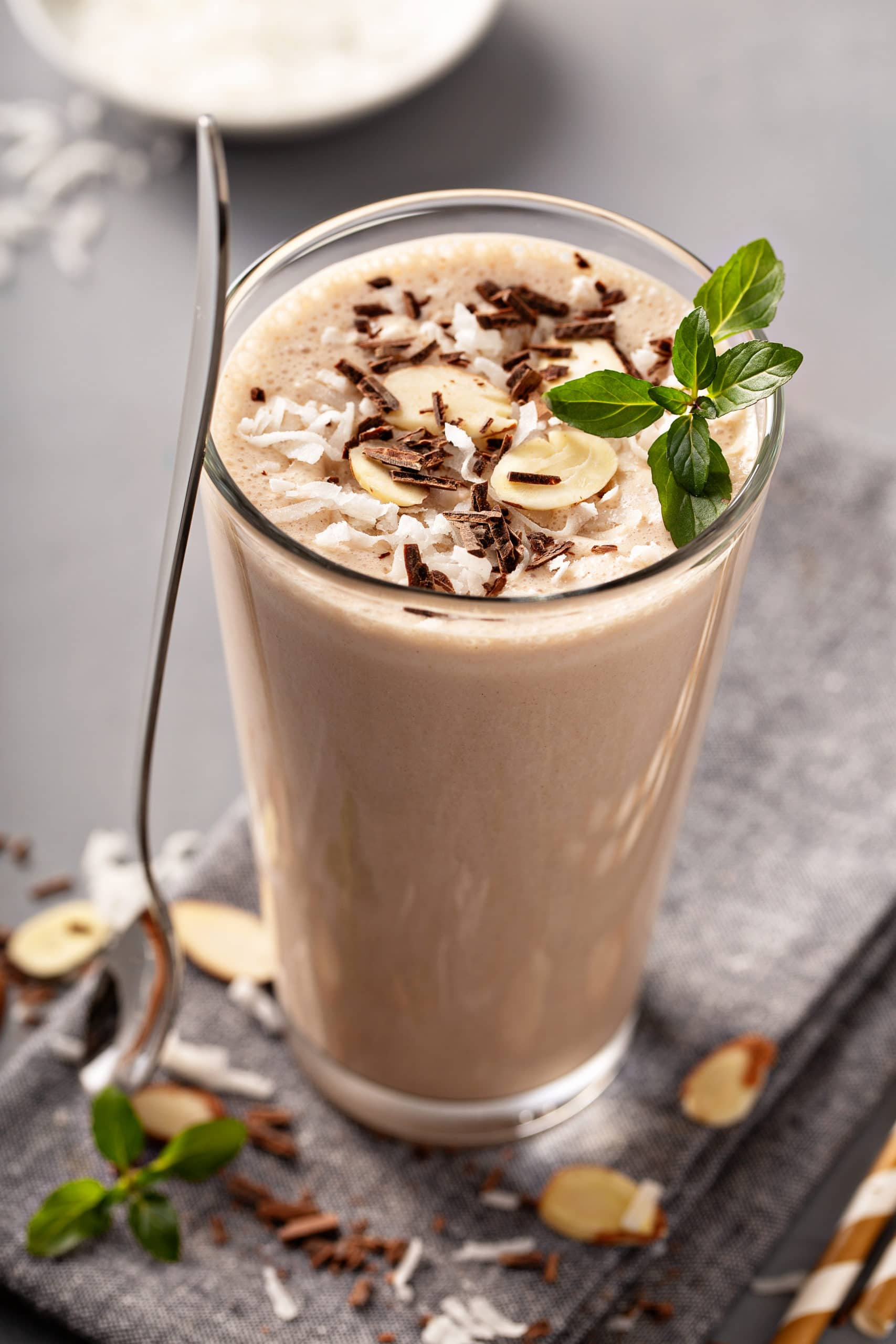 a tall glass of almond joy chocolate coconut protein shake with fresh mint leaves on top and a tall spoon