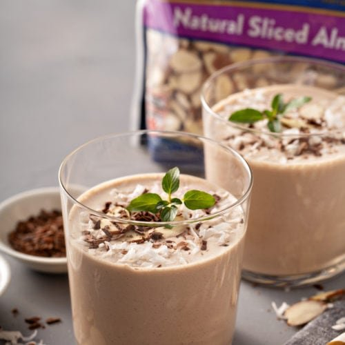 Two glasses of almond joy protein shakes, shaved chocolate, a package of Fisher's slivered almonds, coconut topped with mint leaves