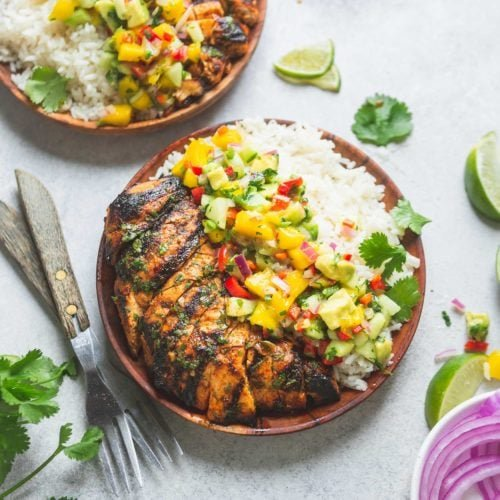 Two dinner plates filled with grilled chicken, coconut rice and mango salsa. The salsa is bright and colorful with chunks of mango and onion, peppers and cilantro. There are sliced red onions, lime wedges and forks on the table.