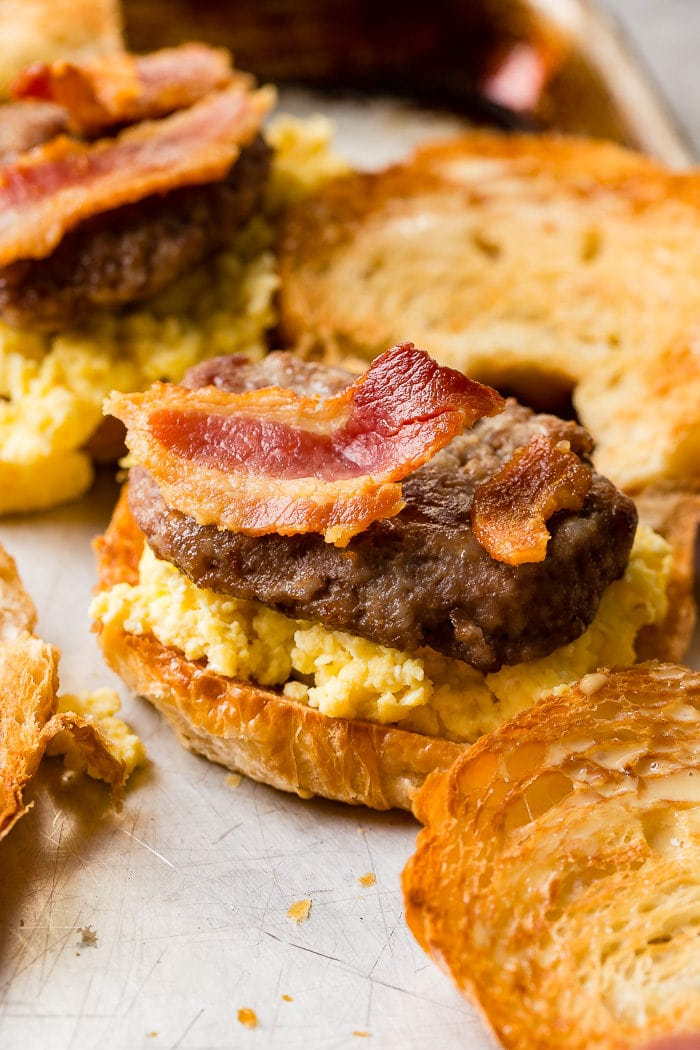 A photo of halved toasted croissants piled with perfectly scrambed eggs, a sausage patty and bacon strips on one half.