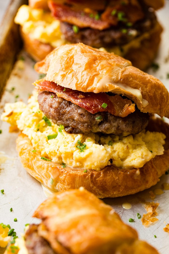 A photo of a breakfast sandwich on a croissant with scrambled eggs, sausage and bacon with chopped chives.