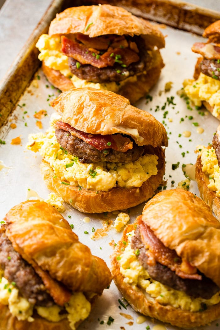 A photo of a sheet pan full of croissant breakfast sandwiches stuffed with eggs, sausage and bacon.
