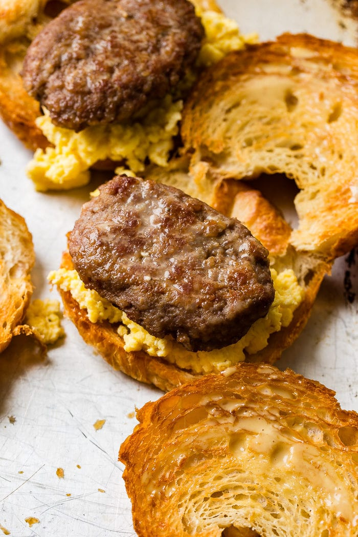 A photo of halved toasted croissants piled with perfectly scrambed eggs and a sausage patty on one half.