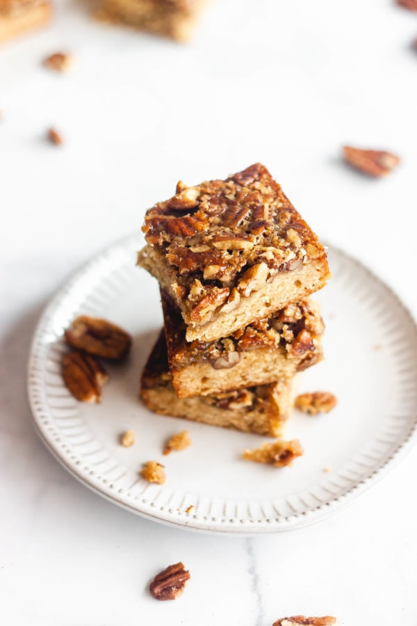 maple pecan pie bars stacked on top of each other on a plate