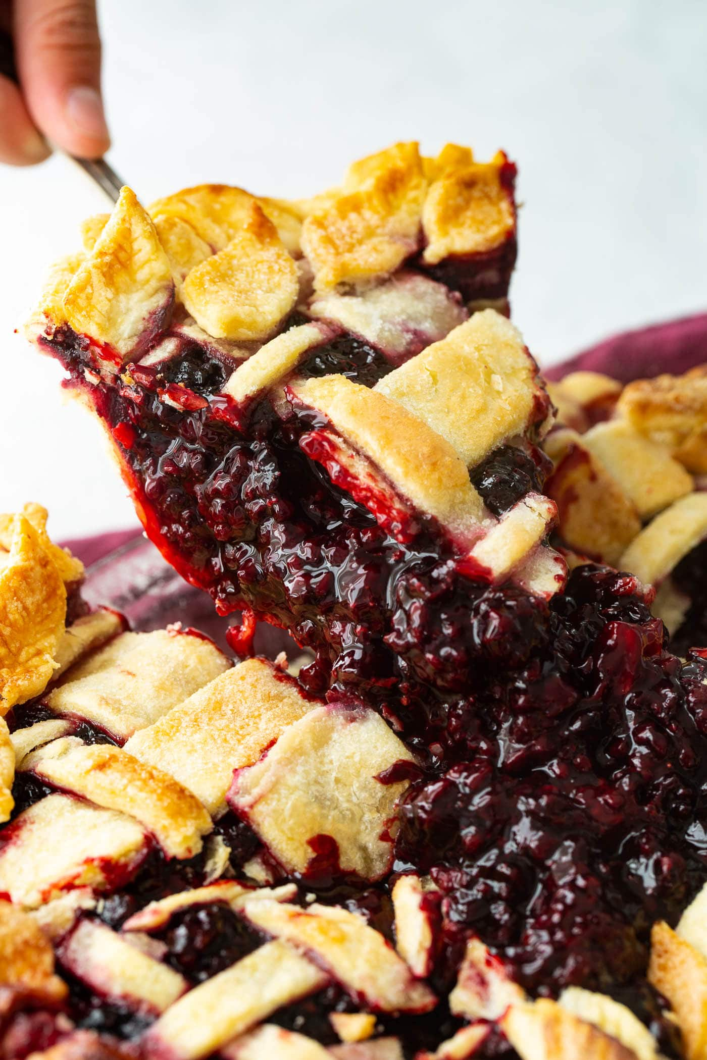 a slice of marionberry pie being lifted out of the pie dish