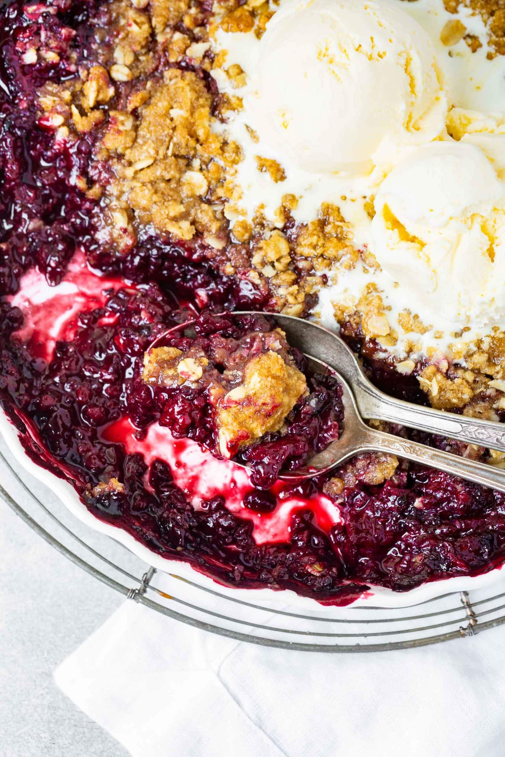 a photo of a pan of marionberry crisp that has been served out of. there are scoops of vanilla ice cream on top that are melting into the crisp.