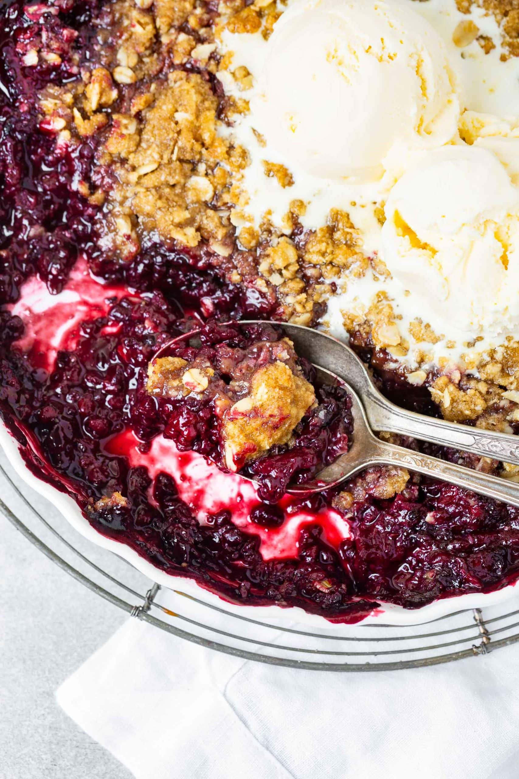 A close up photo of a marionberry crisp that has been served out of. two silver spoons are in the pan and it is topped with two scoops of melted vanilla ice cream.