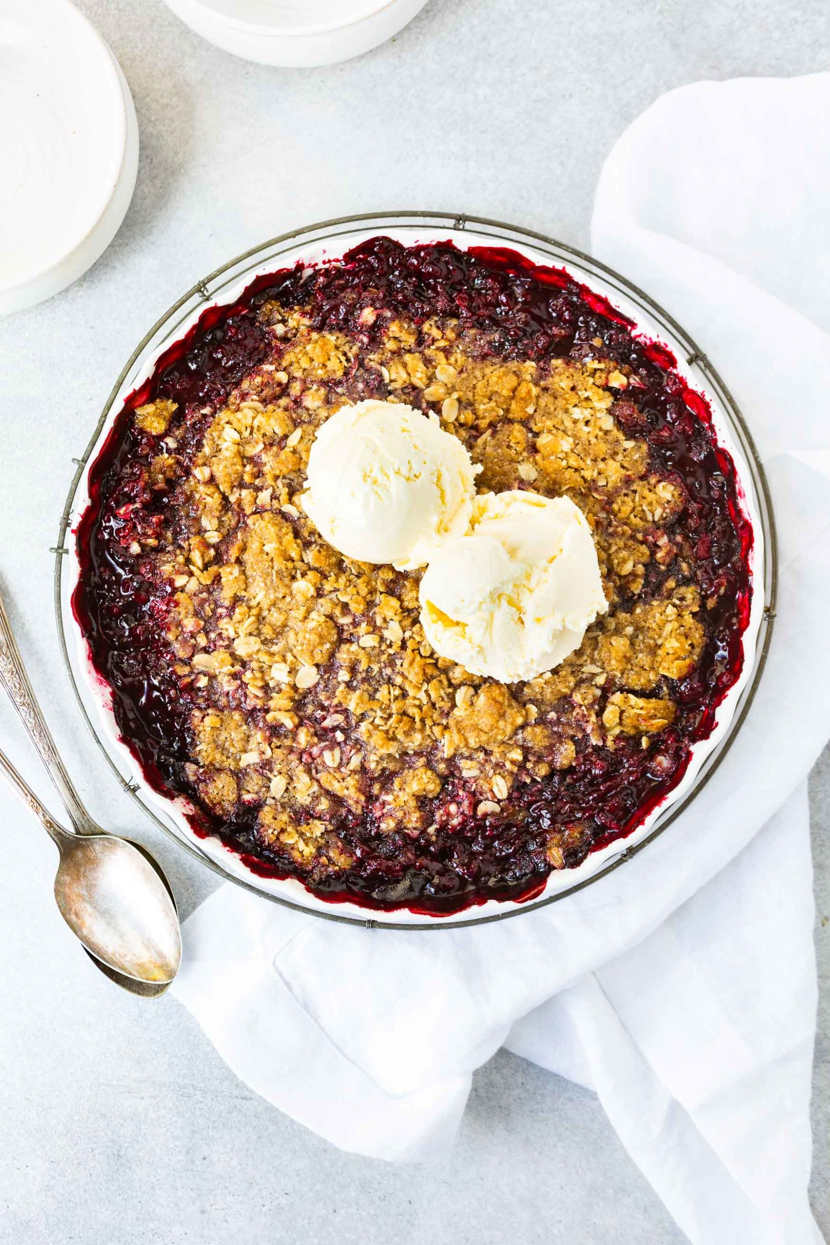 a photo of a whole pan of marionberry crisp topped with two scoops of vanilla ice cream. the pan is circular with a large silver serving spoon sitting next to the pan.