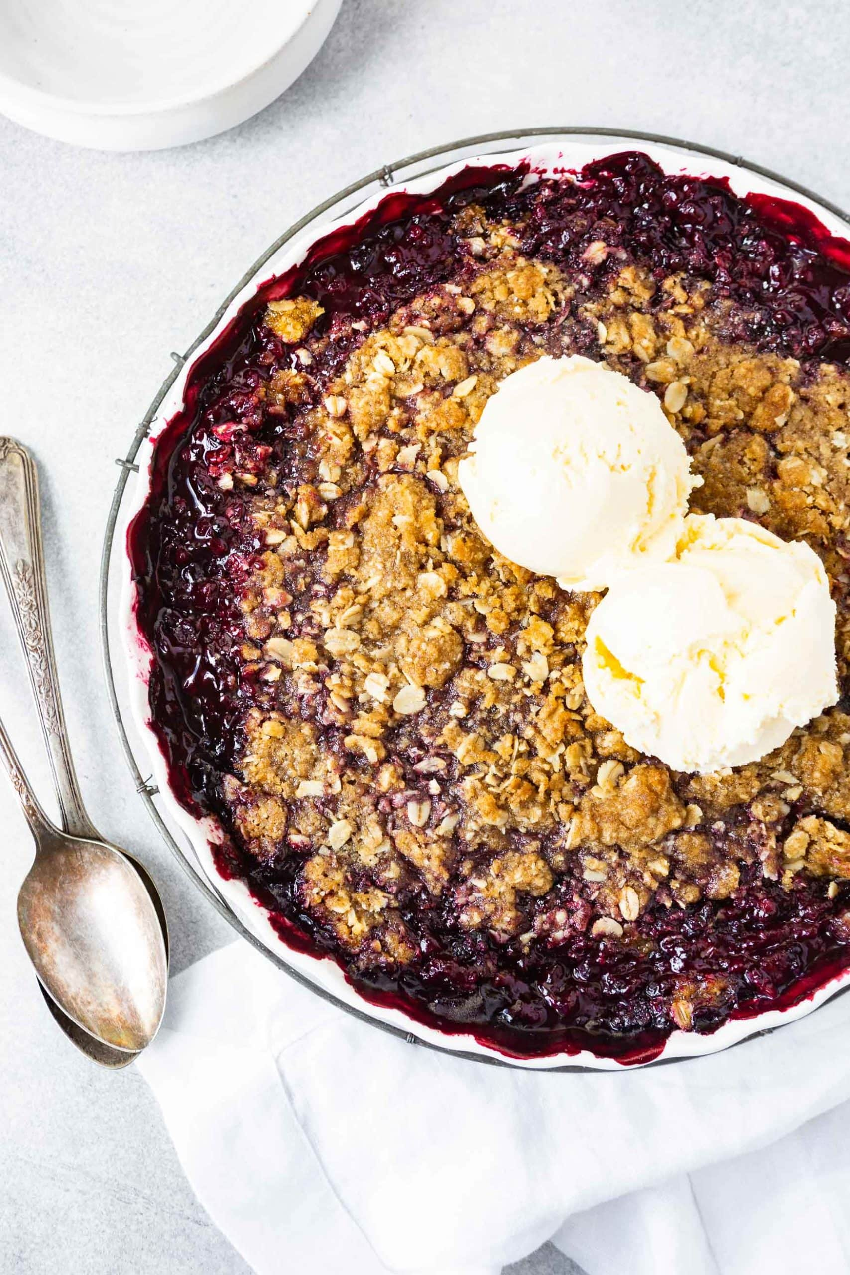 a photo of a whole marionberry crisp in a circular dish topped with two scoops of vanilla ice cream and spoon laying next to the pan.