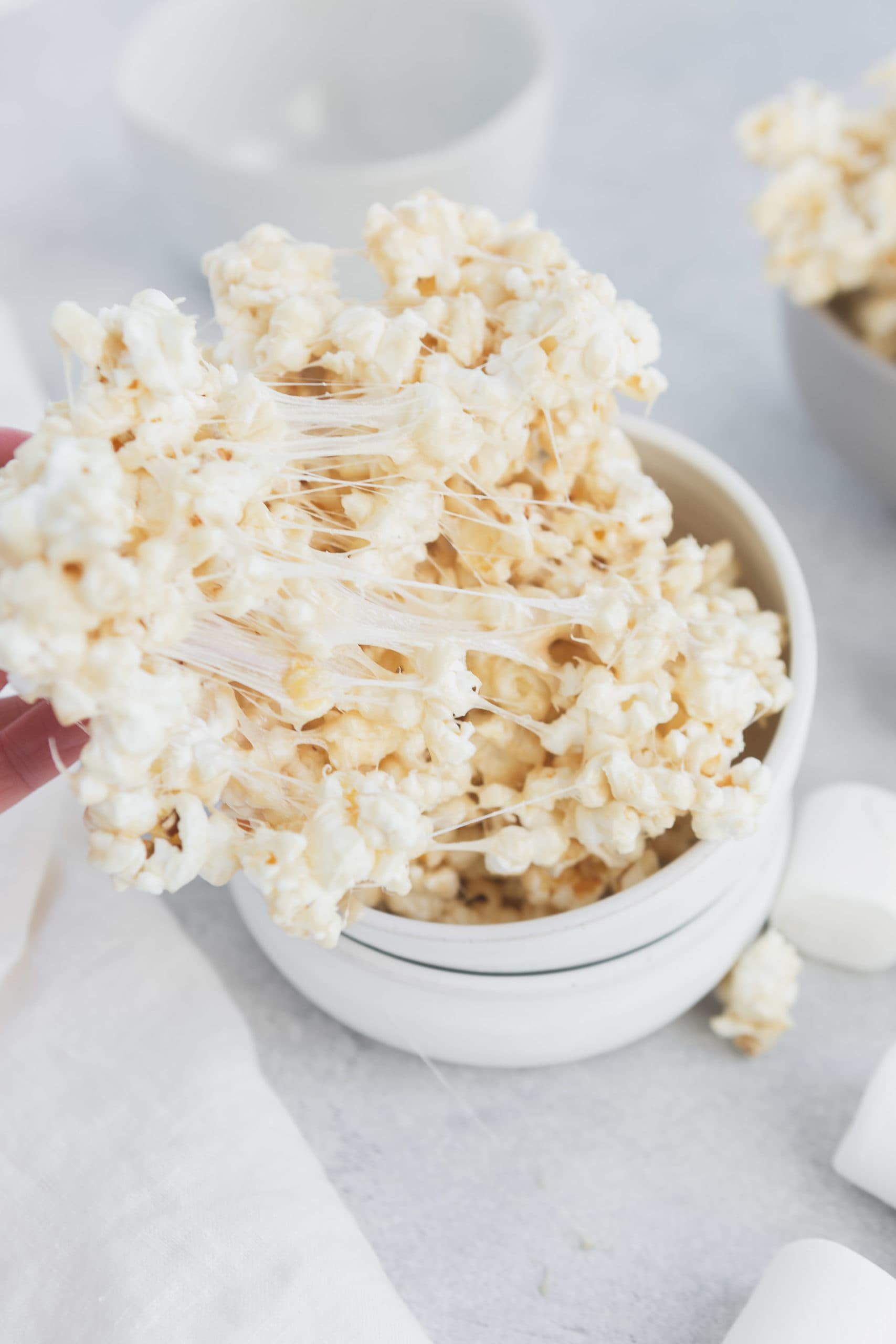 a photo of someone pulling a handful of marshmallow popcorn from a small bowl. The marshmallow is sticky and gooey.