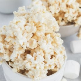 a photo of a small white ceramic bowl filled to overflowing with sticky marshmallow popcorn with another bowl full in the background.