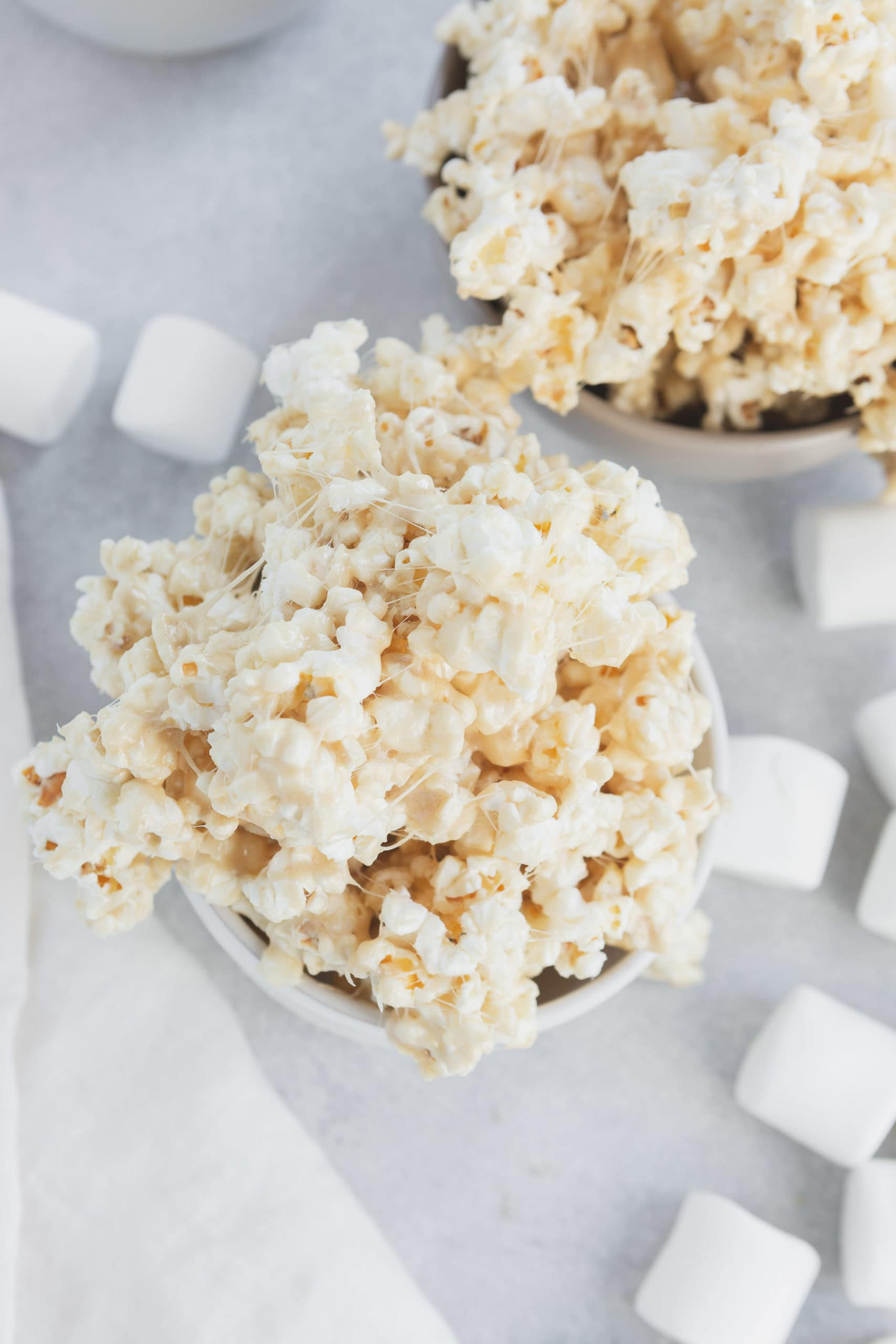 a photo of a small white bowl overflowing with gooey marshmallow popcorn.