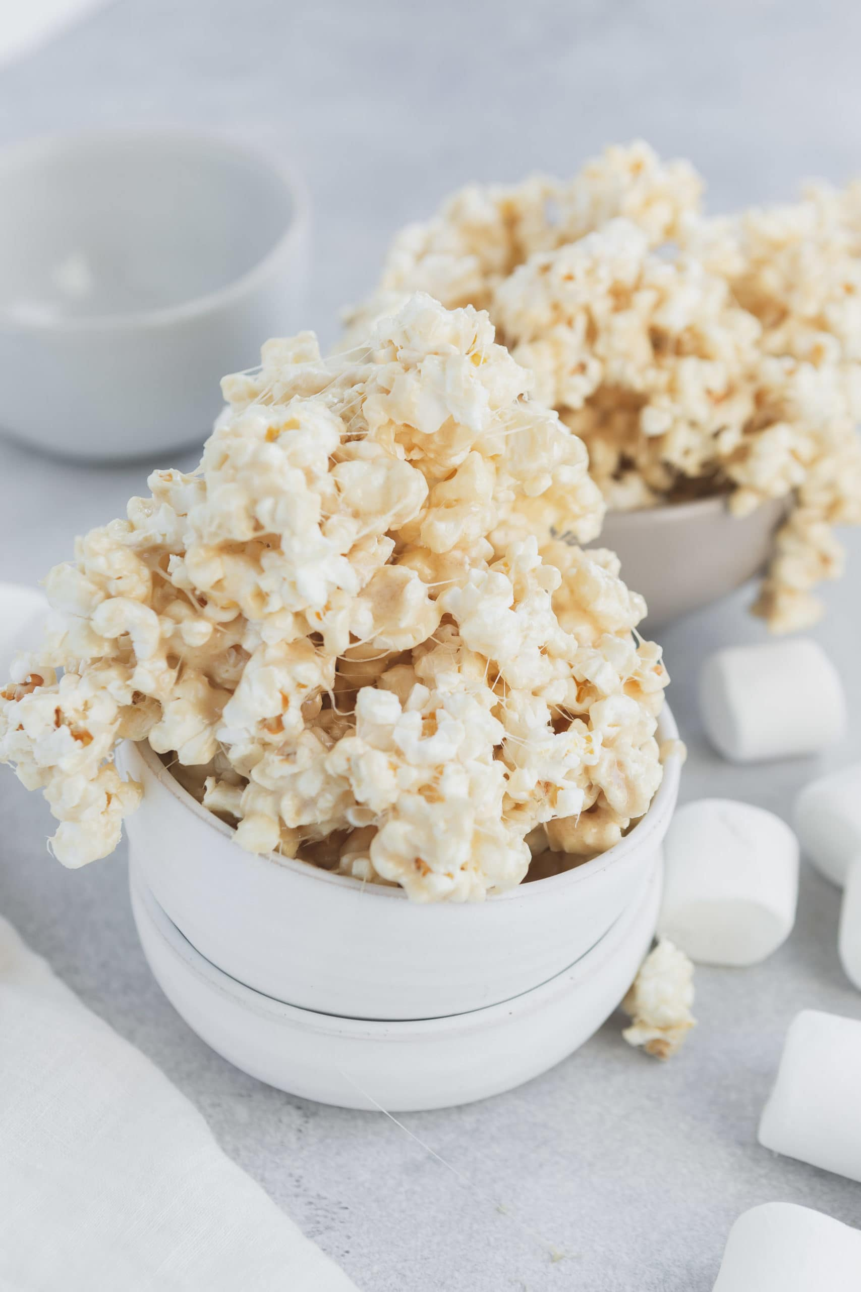 a photo of gooey marshmallow popcorn spilling out of a small white bowl with large marshmallows sprinkled all around and another bowl full in the background.