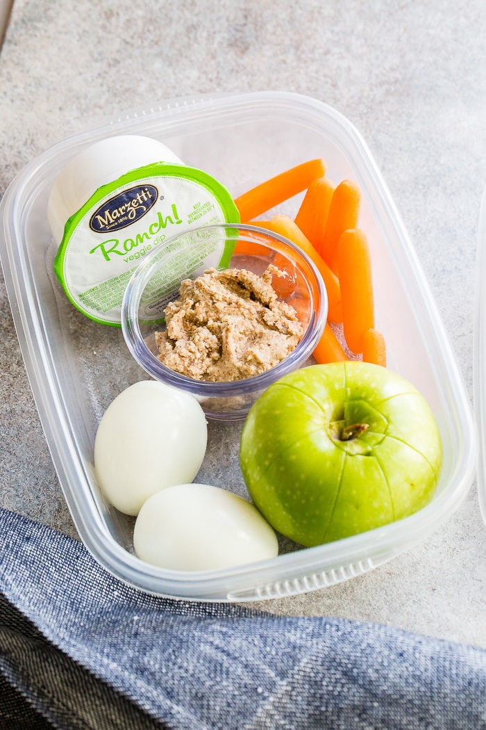 a green granny smith apple tucked in a tupperware next to two hard boiled eggs, almond butter, carrots and ranch snack pack