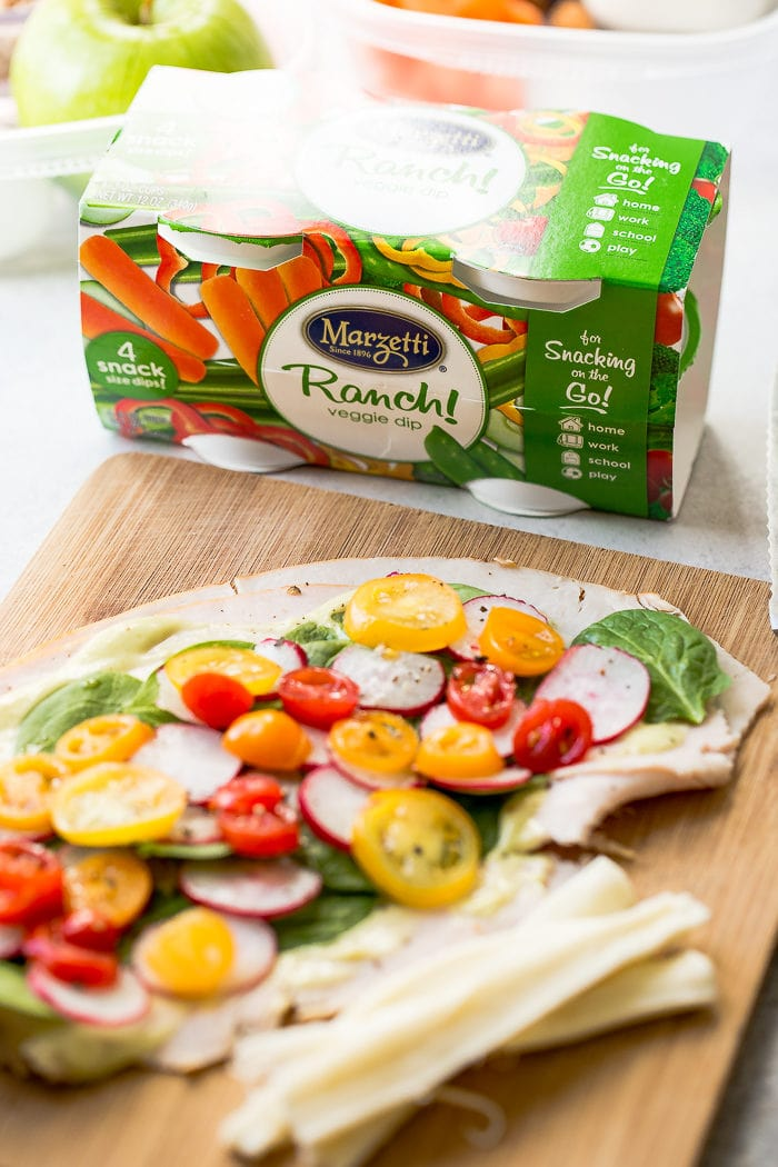 Turkey roll ups with honey avocado dressing, spinach, tomatoes and radishes on a cutting board ready to be rolled up with ranch snack packs behind it