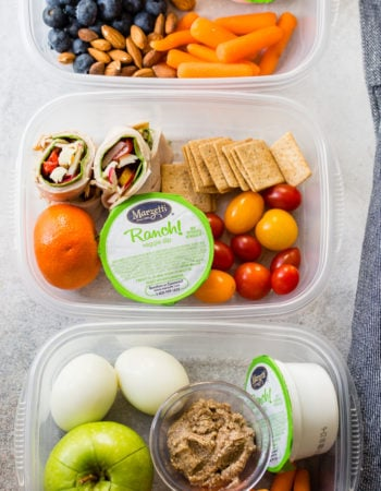 Tupperware packed with turkey rolls ups, ranch snack packs, tomatoes, crackers, oranges, hardboiled eggs, and apples!