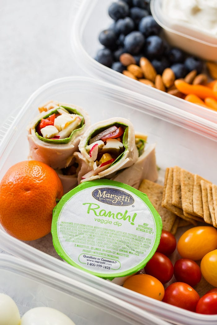 marzetti ranch snack pack in a tupperware with a cutie orange, sliced turkey roll ups, wheat thin crackers and mini tomatoes for a healthy meal prep lunch idea