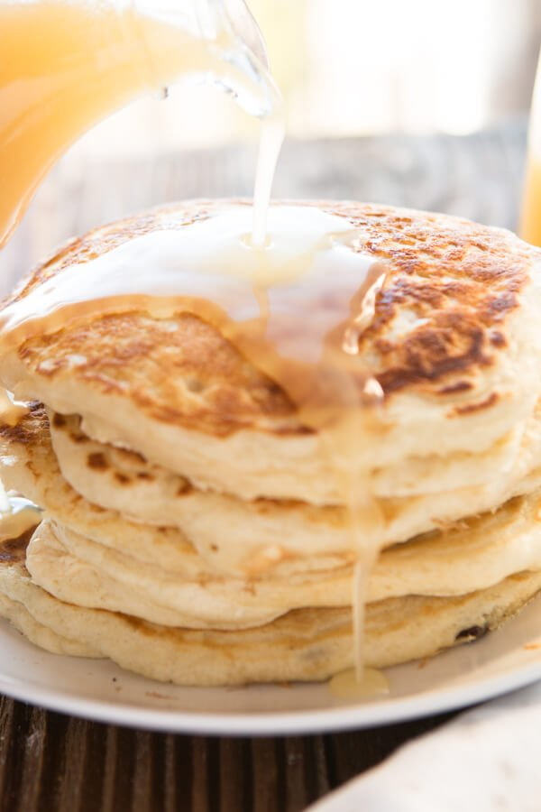 pouring syrup over a stack of buttermilk pancakes