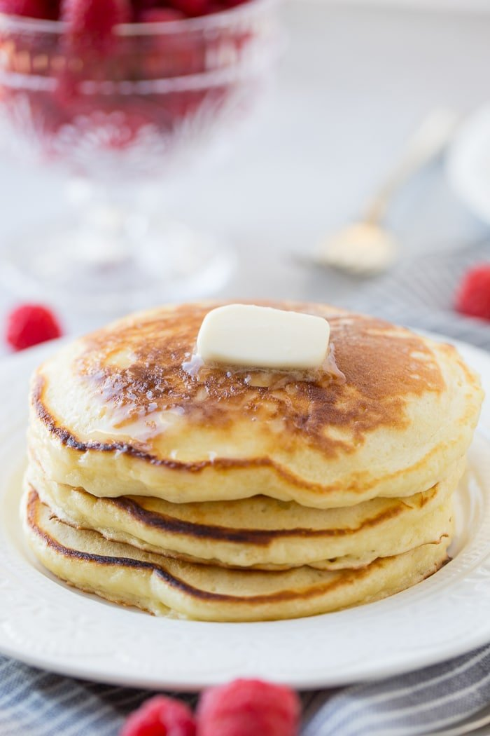 A stack of fluffy homemade sour cream pancakes with a little butter melting on top and a drizzle of syrup dripping down the side. Our recipe for melt in your mouth sour cream pancakes