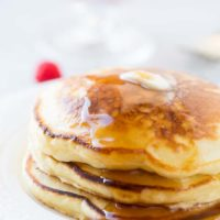 A stack of fluffy pancakes with a little butter melting on top and a drizzle of syrup dripping down the side. Our recipe for melt in your mouth sour cream pancakes