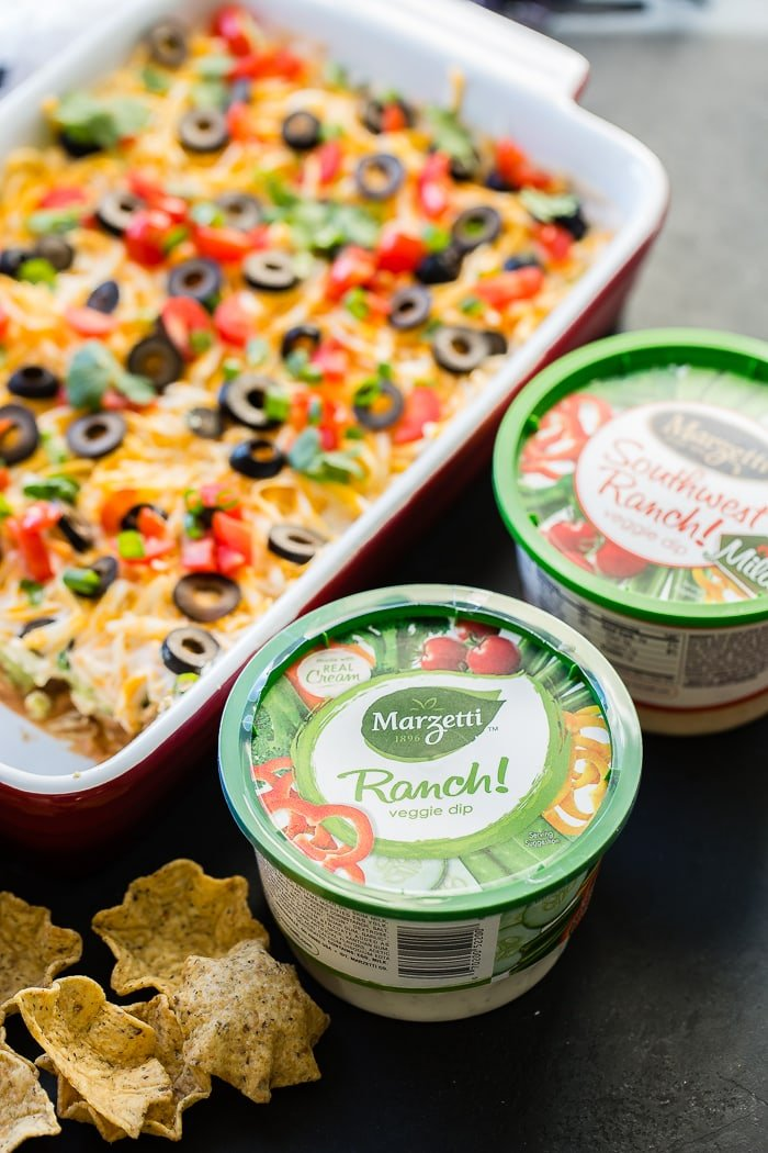 Mexican 7 Layer dip is refried beans, guacamole, southwest ranch, cheese, olives, tomatoes and green onions! ohsweetbasil.com