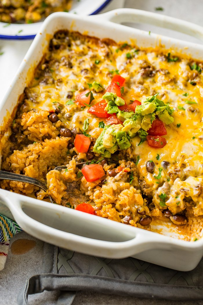 a white casserole dish with a Mexican cheesy ground beef and rice casserole