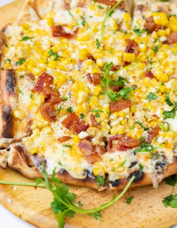 A photo of elote mexican corn grilled pizza with bacon and cilantro on top.