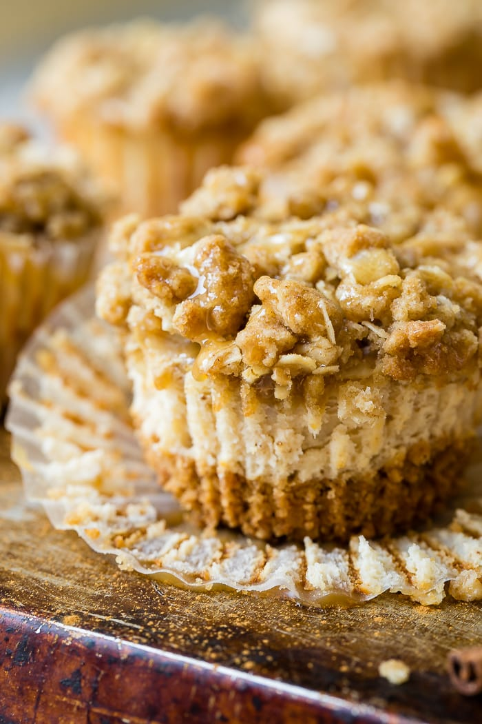 Mini dutch apple cheesecake with a graham cracker crust, creamy cinnamon cheesecake filling, apple pie filling and a brown sugar oat crisp topping sitting on an open cupcake wrapper