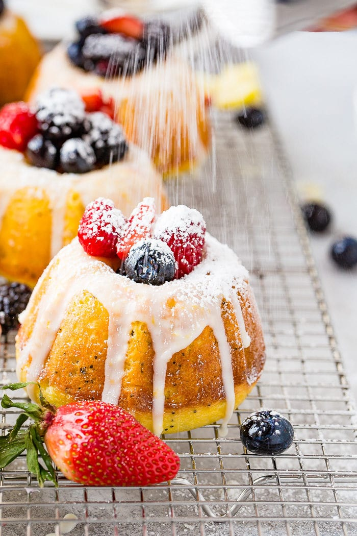 A photo of a mini lemon poppy seed bundt cake on a silver wired cooling rack with a lemon glaze on top and fresh powder sugar being dusted on fresh berries on top.
