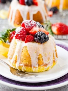 A photo of a mini lemon poppy seed bundt cake on white plate with a lemon glaze on top and fresh powder sugar dusted berries.