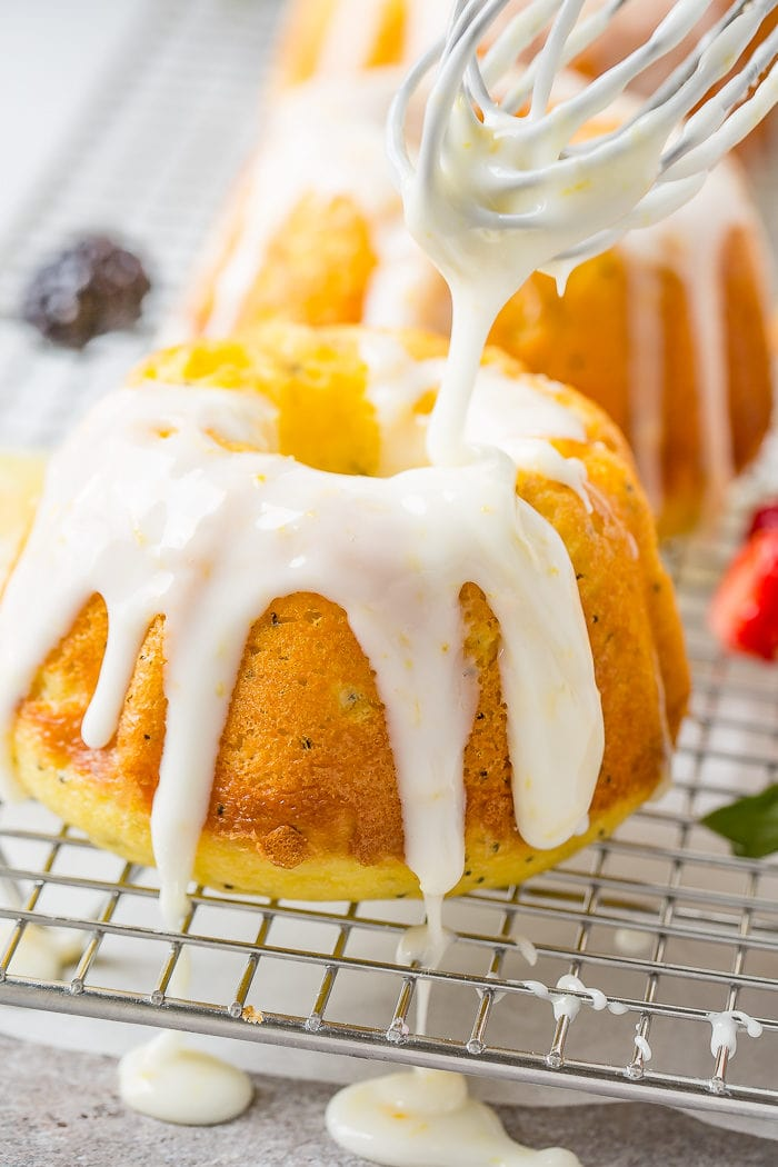 A photo of a mini lemon poppy seed bundt cakes on a silver wired cooling rack with a creamy white lemon glaze being poured on top.