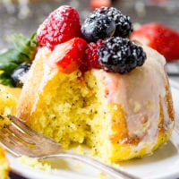A photo of a mini lemon poppy seed bundt cake on on a silver wire cooling rack with a lemon glaze on top and fresh berries.