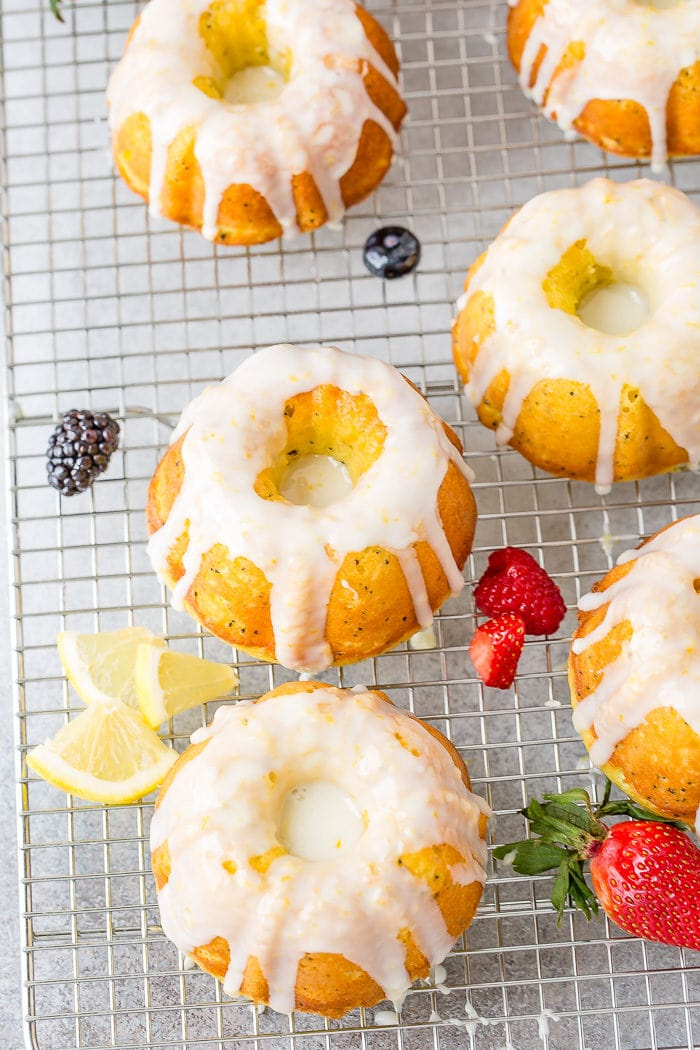 A photo of several mini lemon poppy seed bundt cakes on a silver wired cooling rack topped with a creamy white lemon glaze.