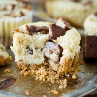 Creamy cheesecakes swirled with caramel and dotted with nuggets of Twix candy bars, these Mini Twix Caramel Cheesecakes are an easy cheesecake recipe!  ohsweetbasil.com