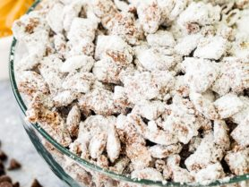 A photo of muddy buddies snack mix in a glass bowl.