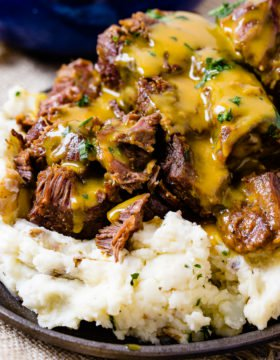 A photo of beef short ribs smothered in mustard Carolina BBQ sauce over a pile of mashed potatoes.