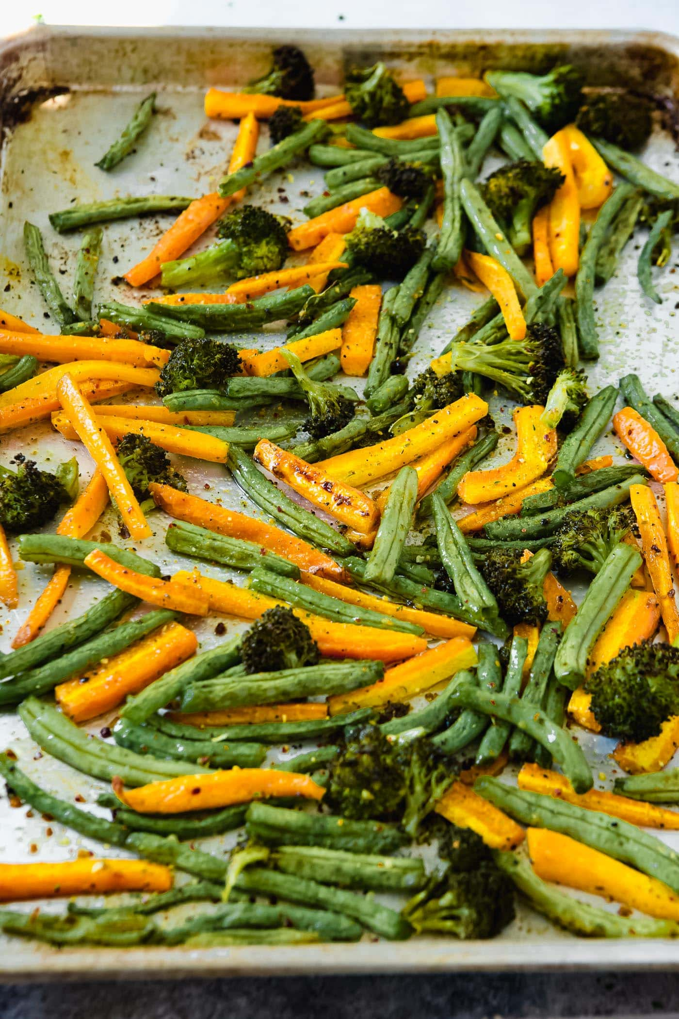 a photo of roasted carrot sticks, green beans and broccoli on a baking sheet.
