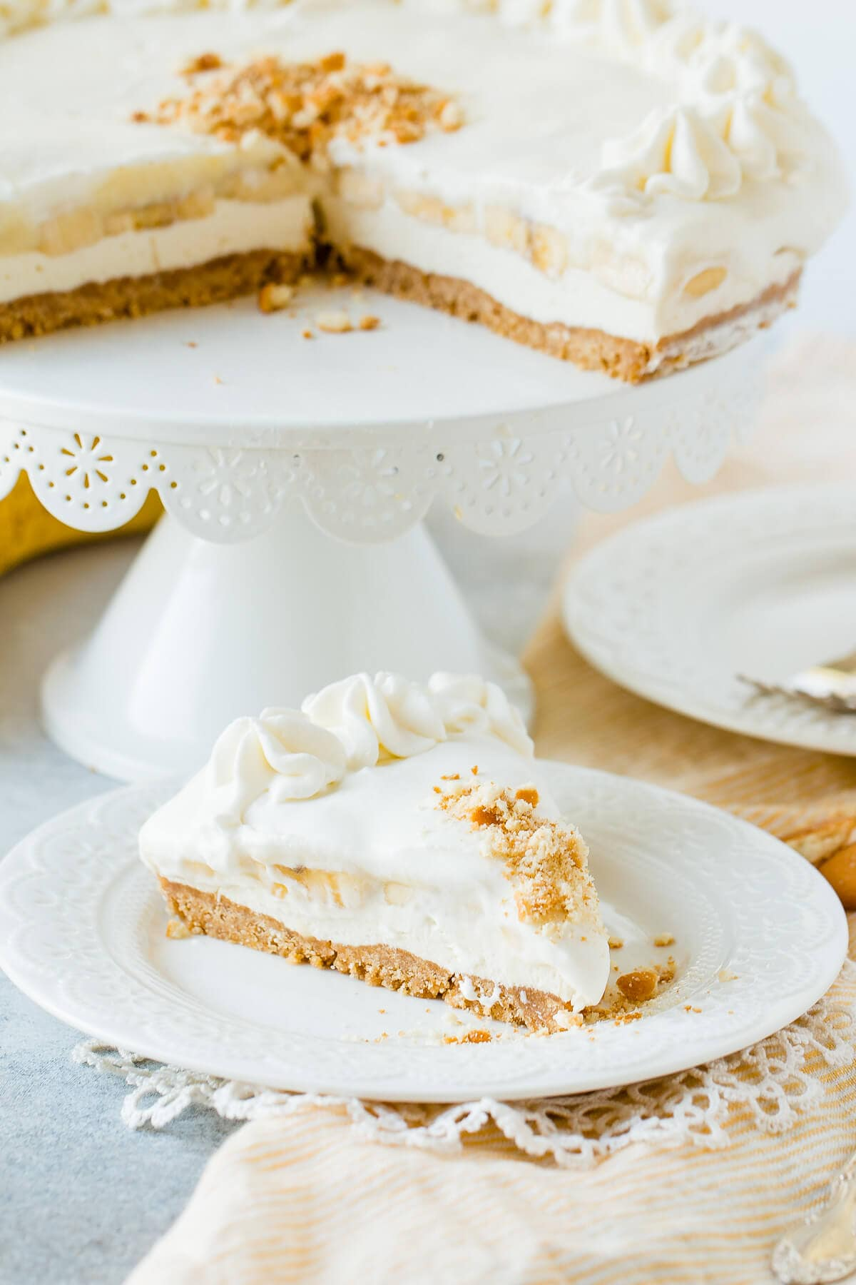 slice of banana pudding cheesecake on plate in front of cake stand