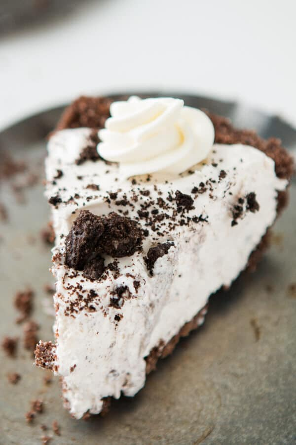 Slice of homemade oreo cream pie with chocolate graham cracker crust on a silver tray.