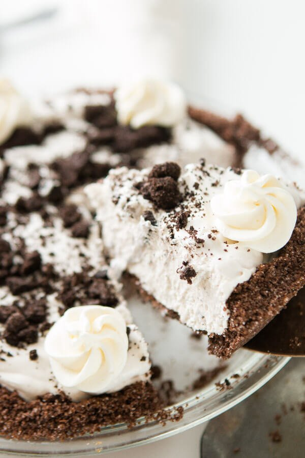 Picking up a piece of this simple no bake oreo pie with chocolate graham cracker crust with a cake knife.