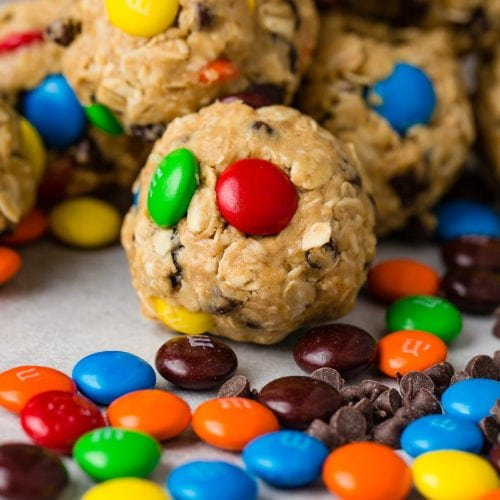 7 protein energy balls packed with oats, raisins, mini M&Ms, and mini chocolate chips. There are mini M&Ms and raisins scattered on the table in front of the protein bars.