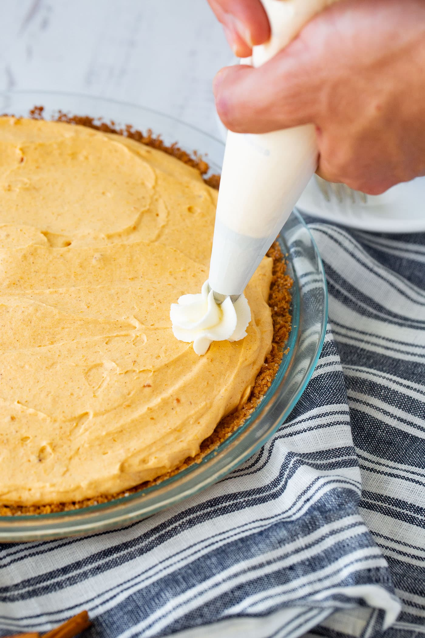 A photo of a no bake pumpkin pie with swirls of whipped cream being piped on top.