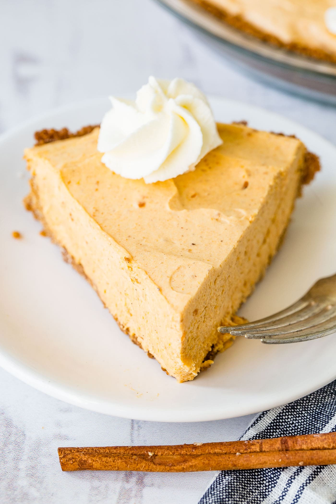 A photo of a slice of no bake pumpkin pie with a swirl of whipped cream on top.