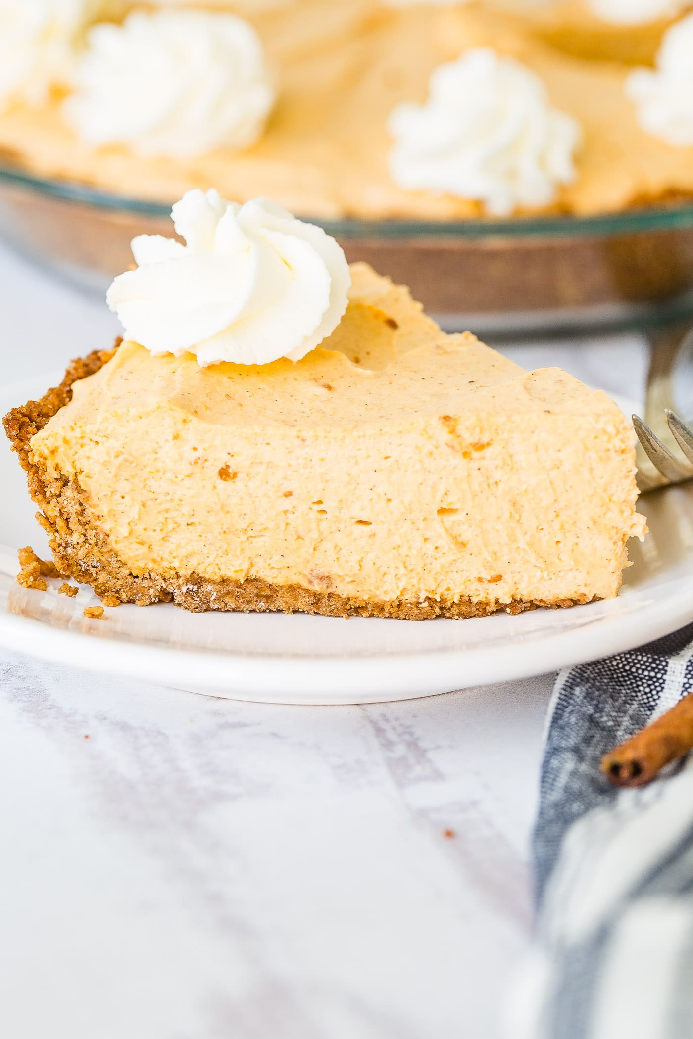 A photo of a slice of no bake pumpkin pie on a white plate with a swirl of whipped cream on top.