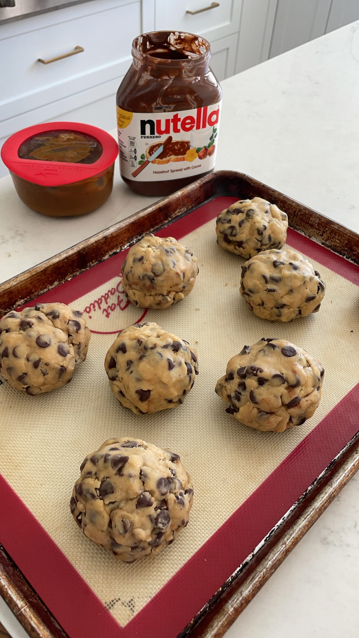 Chocolate chip cookie dough stuffed with nutella and caramel and then pinched closed to bake