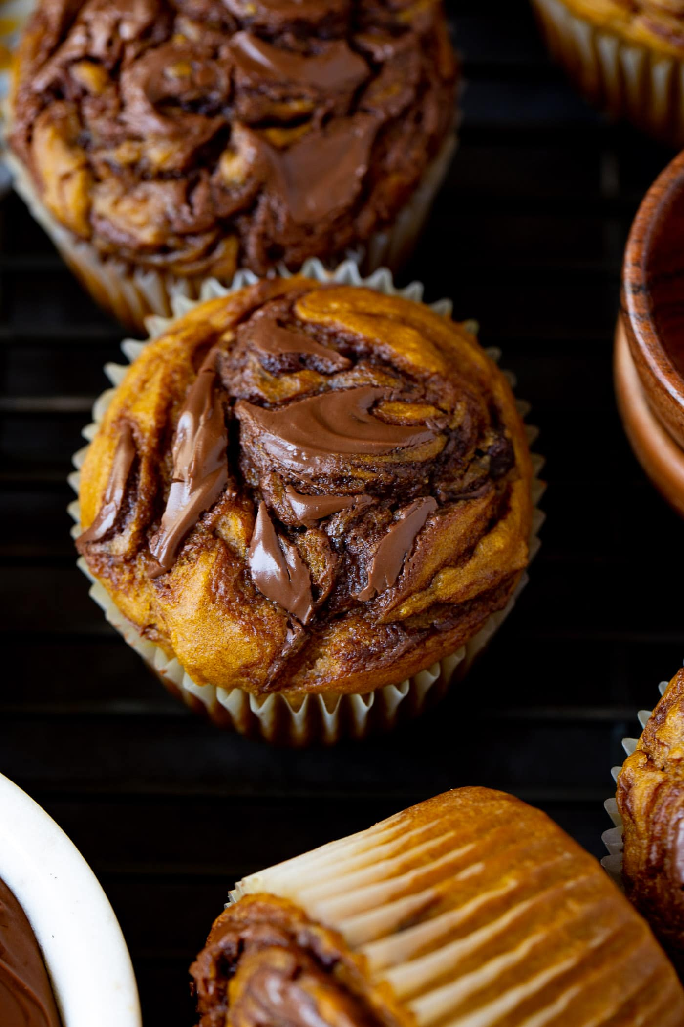 A top view of a Nutella swirled pumpkin muffin. Nutella is swirled through the muffin before it is baked. Other muffins are in the background.
