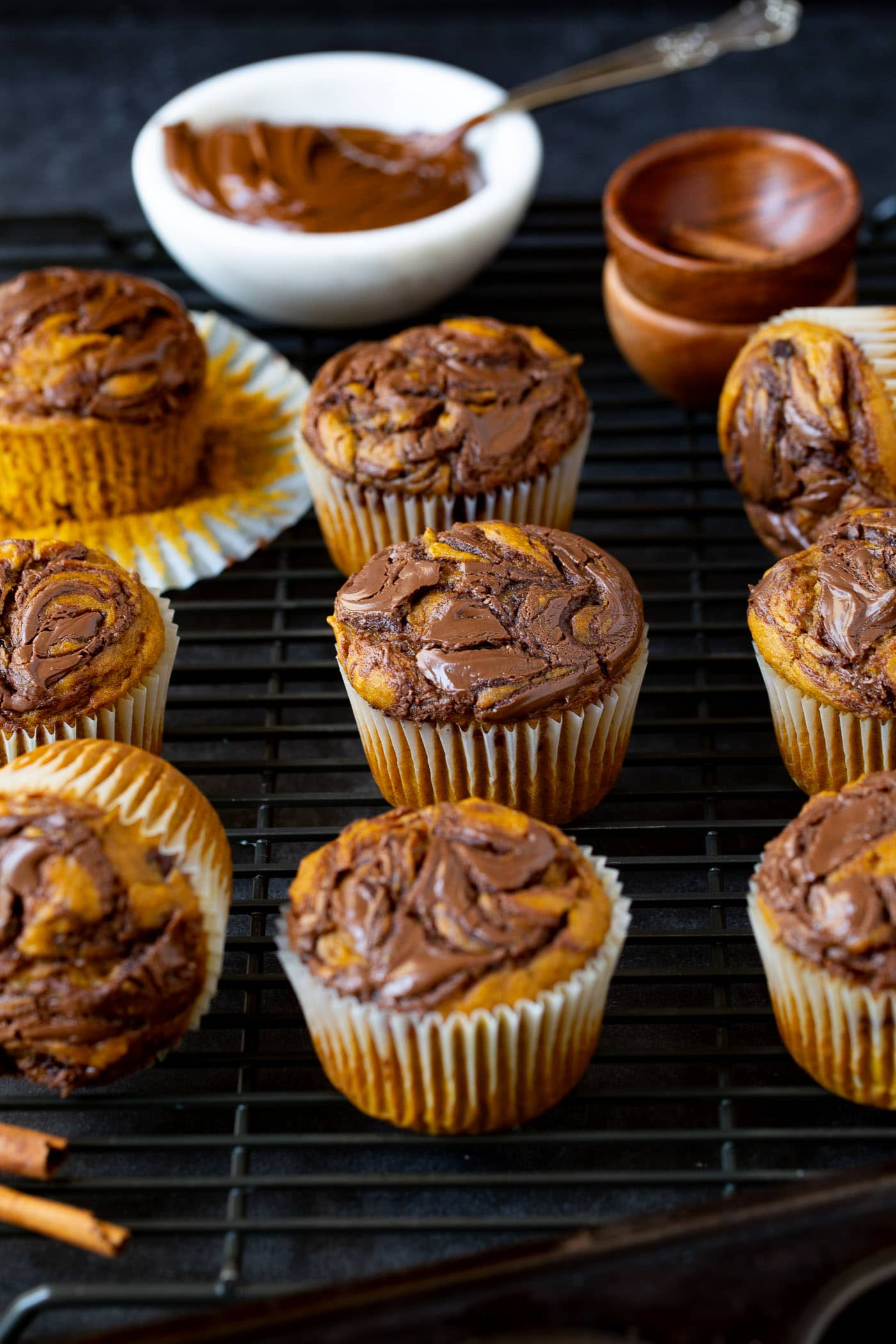ten Nutella swirled pumpkin muffins. The paper liner has been peeled back on one of the muffins, and a small bowl of Nutella is in the background.